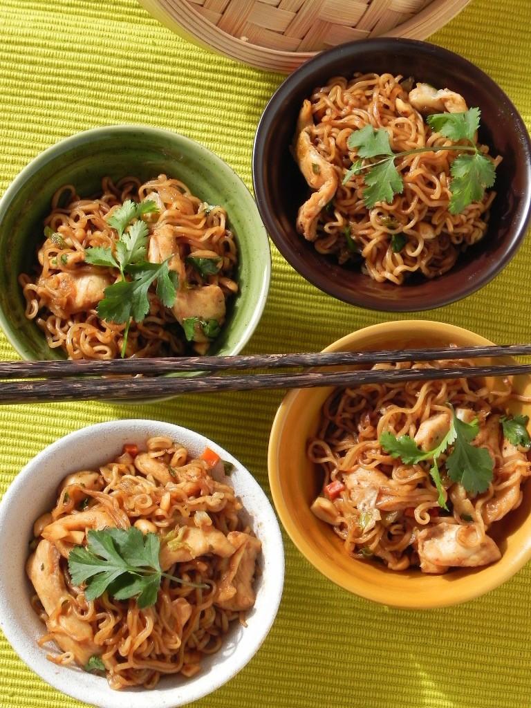 Wok oriental de fideos picantes con pollo, lima y cacahuetes