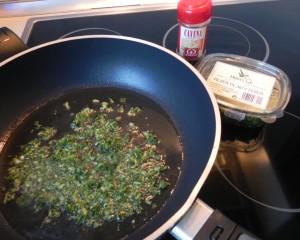 Ponemos en la sartén un poco de aceite, y cuando está caliente, añadimos la picada de ajo y perejil y un par de cayenas