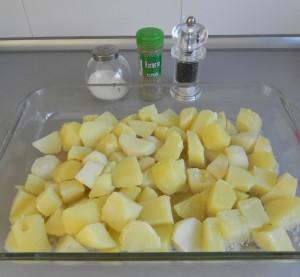 Echamos con cuidado las patatas hervidas al aceite caliente y añadimos el romero, la sal y la pimienta