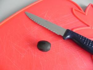 Partimos una aceituna negra por la mitad longitudinalmente