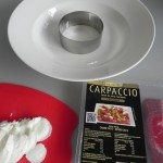 Ponemos un círculo de emplatar en el plato de servir y comenzamos a alternar capas de burrata y de carpaccio