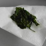 Un vez fritas las hojas de albahaca, las dejamos sobre papel de cocina para quitarles el exceso de garsa