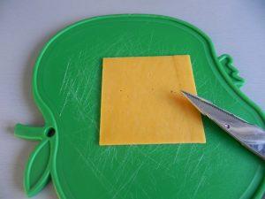 Cortamos los bordes de la loncha de queso