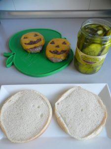 Ponemos un pepinillo en cada pan de hamburguesa a modo del rabito de la calabaza