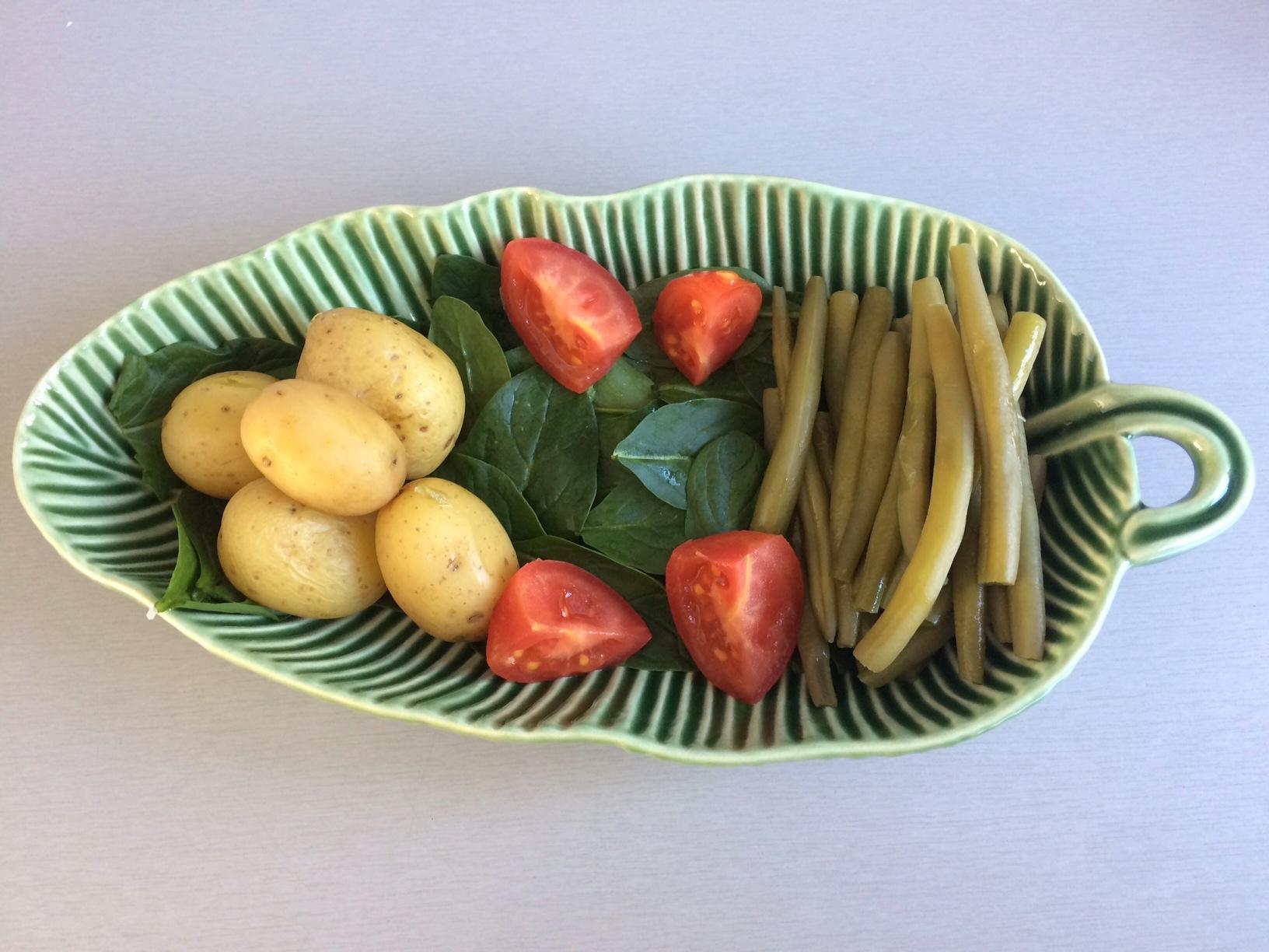 Ponemos encima las judías verdes, las patatas y los cuartos de tomate, dejando un hueco en el centro para el huevo